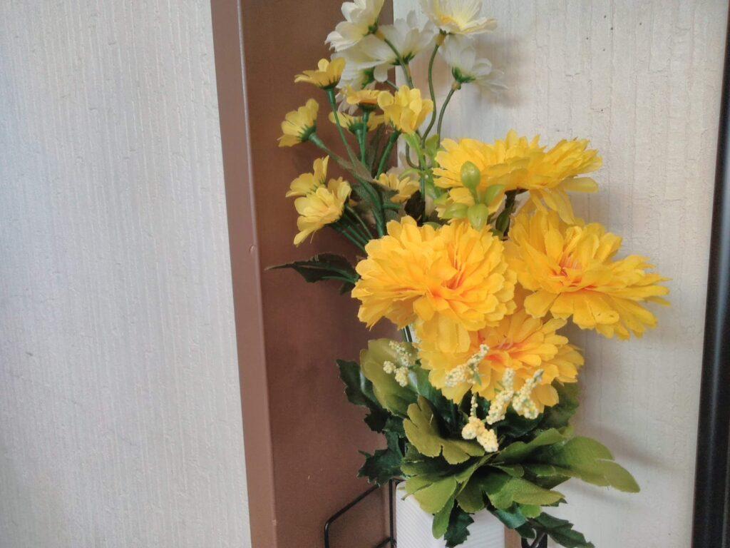 玄関の小さな棚に黄色とピンクの花を飾りました。100均です。